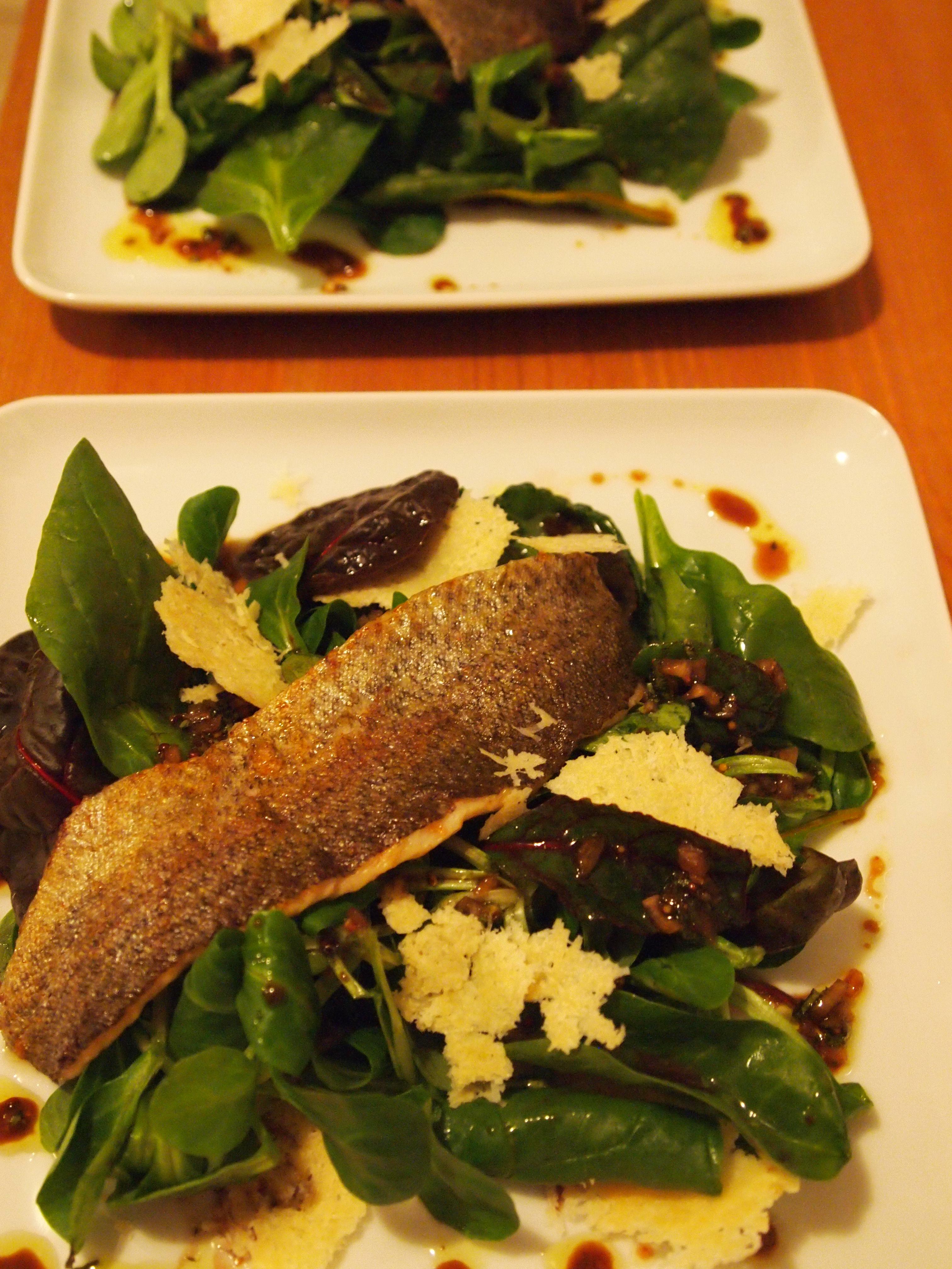 Gebratenes forellenfilet auf blattsalat mit parmesanchips